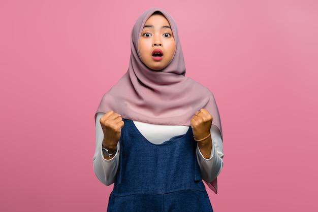 Молодая азиатская женщина шокирована выражением успеха
