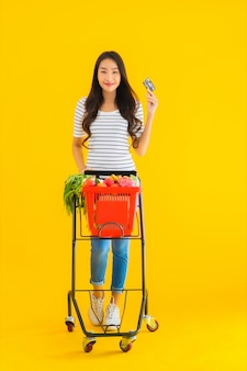 Young asian woman shopping grocery cart from supermarket