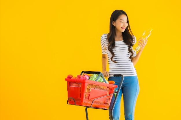 スーパーマーケットとカートから食料品を買い物若いアジア女性