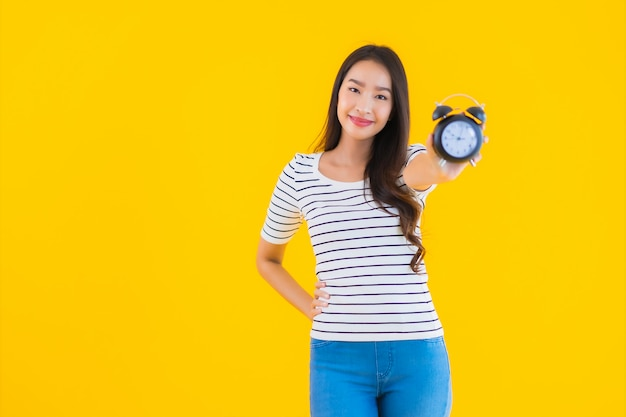 Young asian woman show clock or alarm