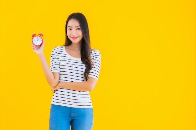 若いアジアの女性の時計またはアラーム