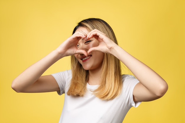 Young asian woman show heart hand sign isolated on yellow background.