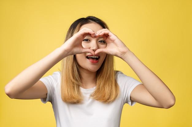 Молодая азиатская женщина показывает знак рукой сердца