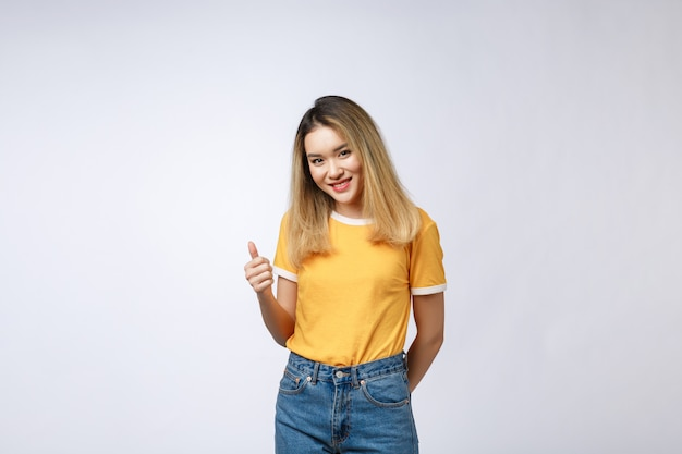Young asian woman show thumbs up on white background.