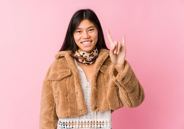 Молодая азиатская женщина показывая жест рожков