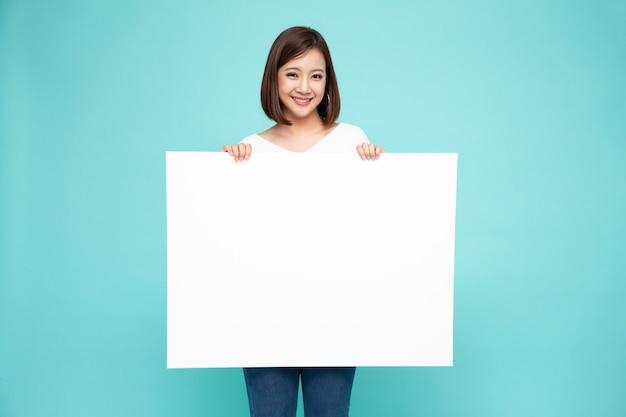 젊은 아시아 여자 보여주는 녹색 벽에 고립 된 빈 흰색 빌보드를 들고