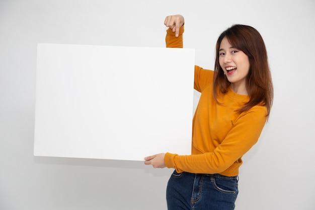Молодая азиатская женщина показывает и держит пустой белый рекламный щит, изолированный на белой стене