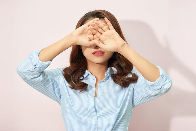 若いアジアの女性がアイスクリームで表示し、淡いピンクで隔離の笑顔