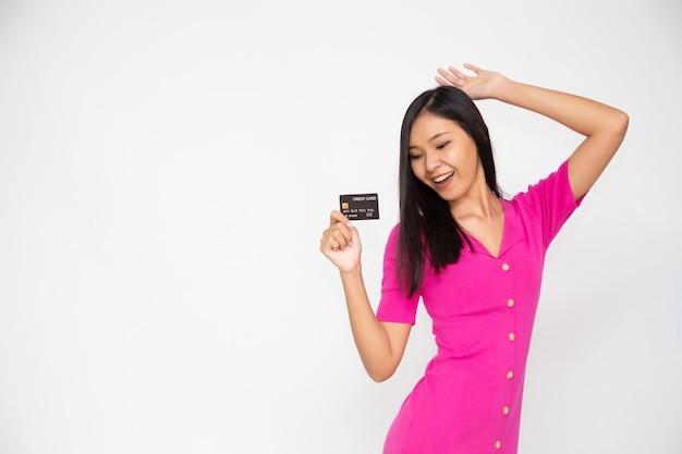 흰색 바탕에 신용 카드를 보여주는 젊은 아시아 여자