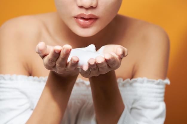 주황색 배경 위에 목욕 수건을 끼고 손에 거품 클렌저를 보여주는 젊은 아시아 여성.