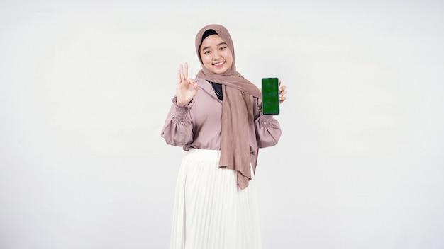 Молодая азиатская женщина показывает экран своего смартфона и хорошо изолирована на белом фоне