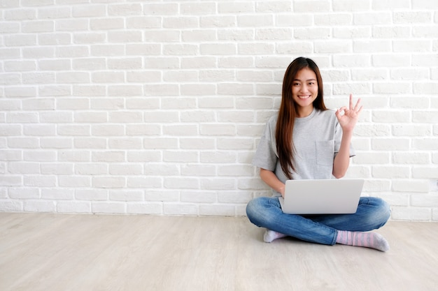 Young asian woman showing ok hand sign and smiling while working with laptop computer in white room