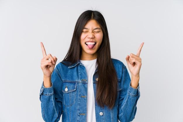 Молодая азиатская женщина показывая жест утеса с пальцами