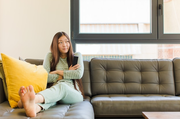 어깨를 으쓱하고, 혼란스럽고 불확실한 느낌, 팔을 교차하고 의아해 보이는 젊은 아시아 여성