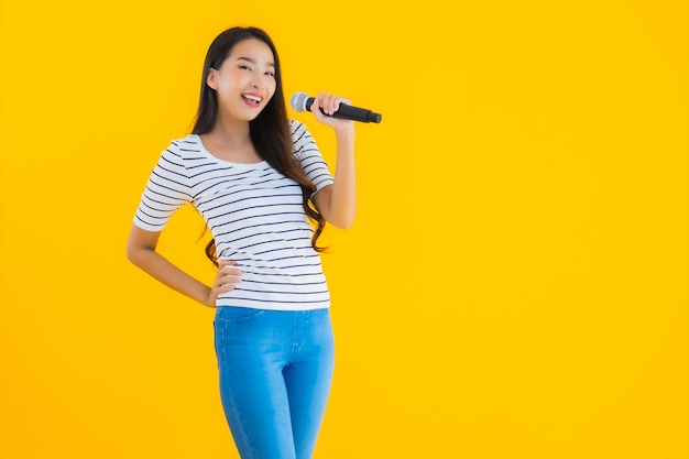 Молодая азиатская женщина поет с микрофоном