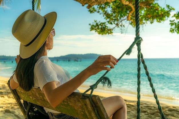 Молодая азиатская женщина сидит и ослабляет на качелях на взморье на летних каникулах. летние флюиды. женщина путешествует одна на отдыхе. backpacker на тропическом пляже рая.