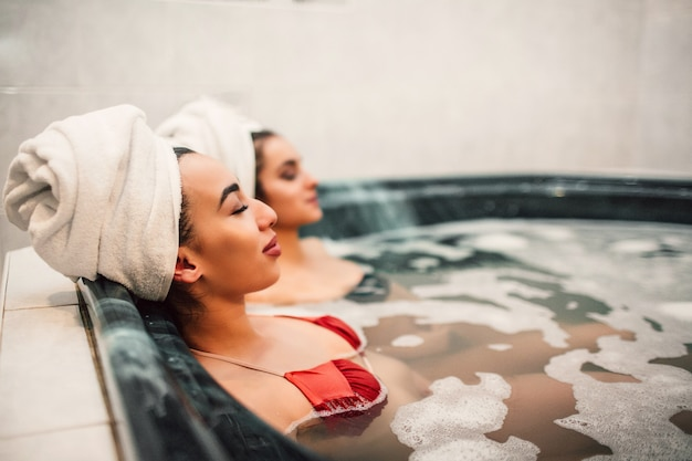 Молодая азиатская женщина сидит в гидромассажной ванне со своим европейским другом. они охлаждают и держат глаза закрытыми. модели носят купальники.