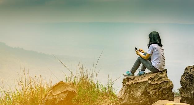 若いアジア人の女性が崖の上の岩の上に座って、スマートフォンのメッセージを使用して