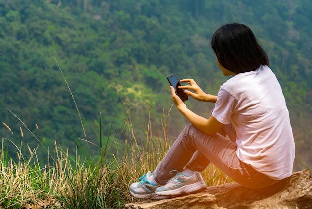若いアジア人女性が崖の上の岩の上に座ってスマートフォンを使う