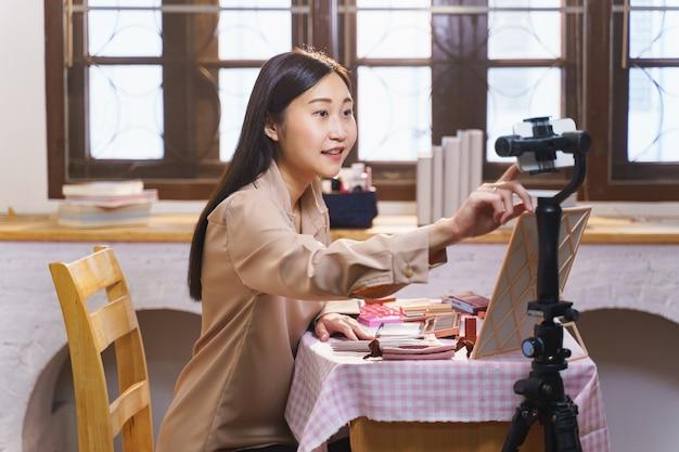 座って、自宅の携帯電話でメイクアップチュートリアルをあきらめる若いアジアの女性。屋内で化粧品についてストリーミングするオンラインコンテンツクリエーターとしてスマートフォンと話している女性