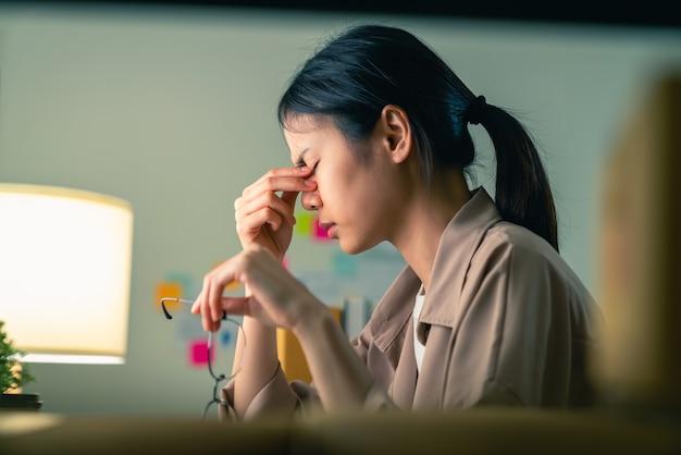 座って、手で眼鏡を保持している若いアジアの女性が眉に触れる