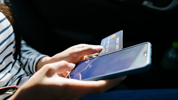 車の後部座席に座って、携帯電話を使用して手でクレジットカードを保持している若いアジア女性。