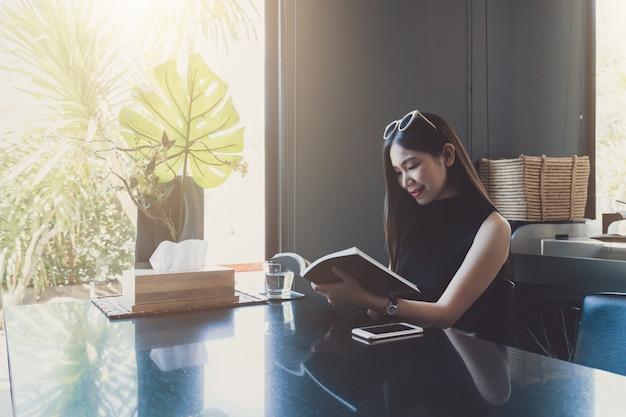Young asian woman sitting enjoying reading book while relaxing
