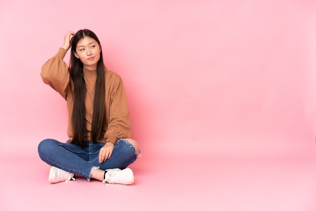 Young asian woman sitting on the floor