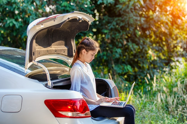 Young asian woman sitting on hatchback car with notebook