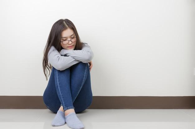 膝を抱いて座っている若いアジア人女性は、部屋で孤独を感じます。