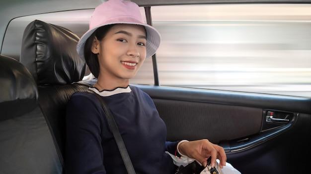 Молодая азиатская женщина сидя в автомобиле и усмехаясь