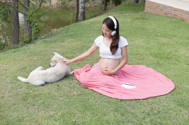 音楽を聴くと白い犬と遊ぶ新鮮な春の草に座っている若いアジア女性。