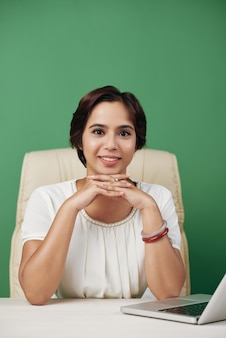 Young asian woman sitting in office chair at desk with laptop and posing with clasped hands