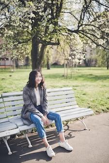 공원에서 피 나무 아래 벤치에 앉아 젊은 아시아 여자