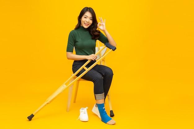 Молодая азиатская женщина сидит на стуле и растягивает ногу с помощью костылей и показывает знак ок, изолированные на желтом фоне, концепция личной аварии