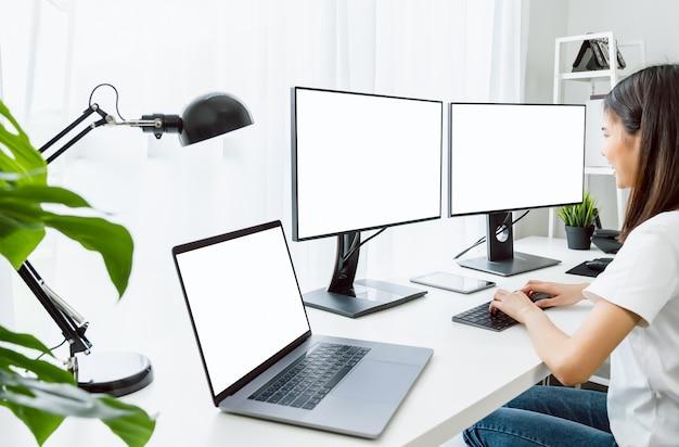 Молодая азиатская женщина, сидящая на стуле и работающая за компьютером с пустым экраном дома в дневное время, светила днем.