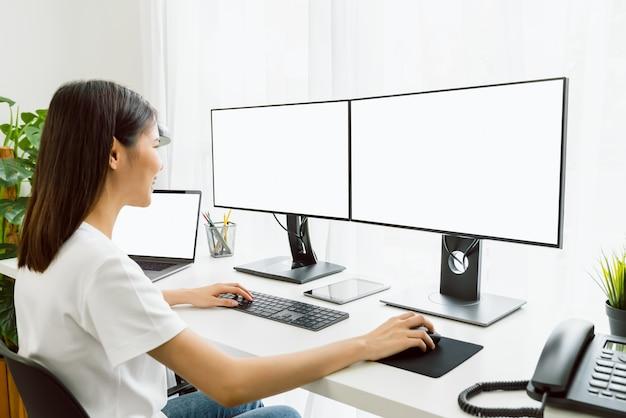 Молодая азиатская женщина, сидящая на стуле и работающая за компьютером