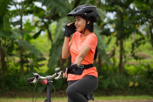彼女の自転車に座って電話で話している若いアジアの女性