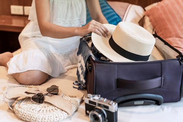 Молодая азиатская женщина сидя на кровати и пакуя ее чемодан подготавливая для перемещения на летних каникулах