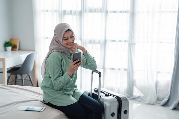彼女の携帯電話とスーツケースを保持しているベッドの上に座っている若いアジア女性