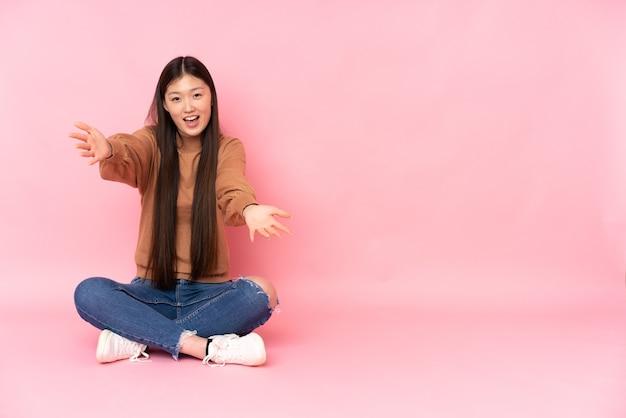 Молодая азиатская женщина сидит на полу, изолированном на розовом фоне, представляет и приглашает прийти с рукой