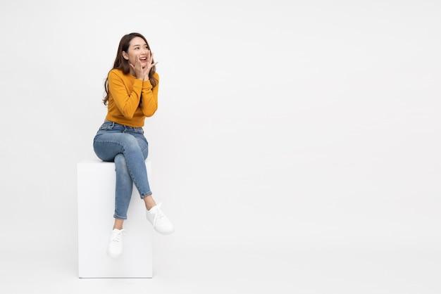 흰색 배경 위에 절연 흰색 상자에 앉아 젊은 아시아 여자