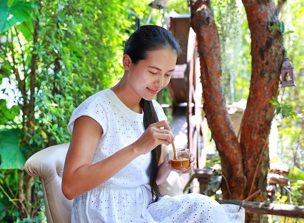 Young asian woman sitting at the outdoor cafe and drinking coffee