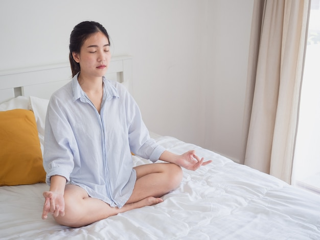 Young asian woman sitting and practicing doing yoga on bed