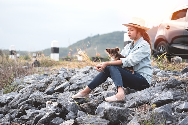 Young asian woman sitting with chihuahua dogs with black hatchback eco car.