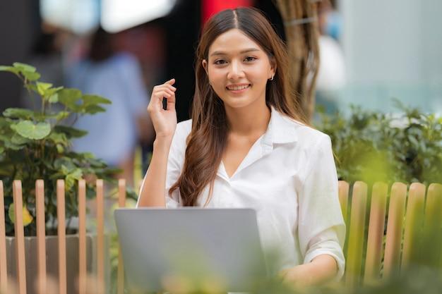 Молодая азиатская женщина, сидящая со смайликом, используя ноутбук в открытом городе