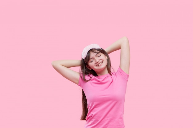 Young asian woman in sleeping eye mask yawning and holding alarm clock isolated on pink. sleepless night