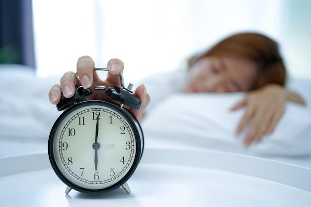 ベッドで寝ている若いアジア人女性は、朝、クリアな目覚まし時計のスヌーズボタンを手で押しました。週末のリラックスコンセプト