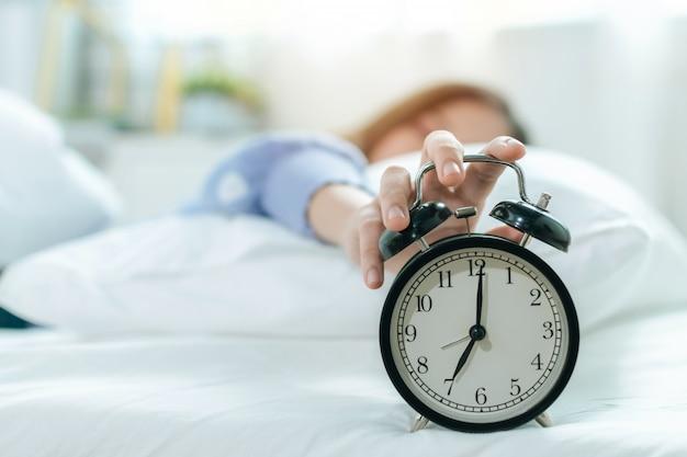 Молодая азиатская женщина спит на кровати, нажимая кнопку повтора на черном винтажном будильнике в семь часов утра в спальне дома, образ жизни, доброе утро, здоровый сон и радостные выходные