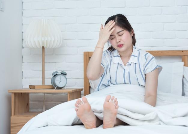 ベッドで寝ている若いアジア女性